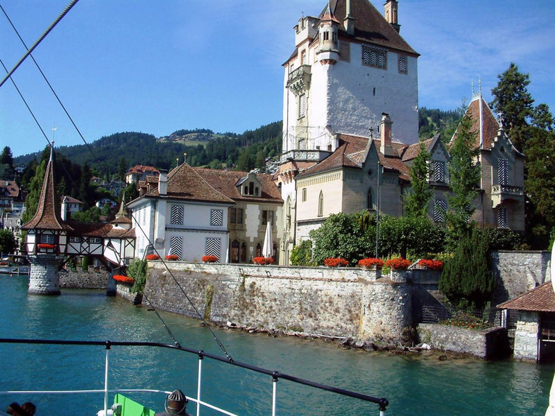 View from paddle steamer Blumlisalp sailing close by the almost fairytale-like castle at Oberhofen