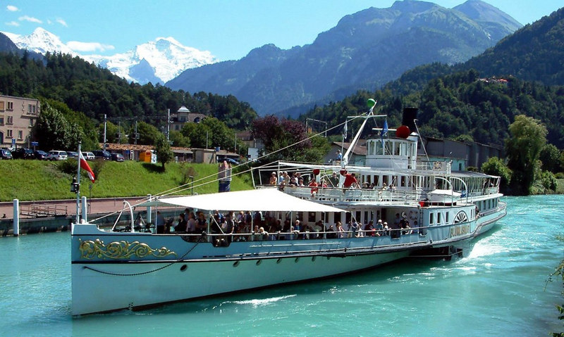 Paddle steamer Blumlisalp arriving at Interlaken West. Her mast is folded back to allow her to pass under a road bridge over the canal. The snow covered mountains in the background are Monch and Jungfrau.