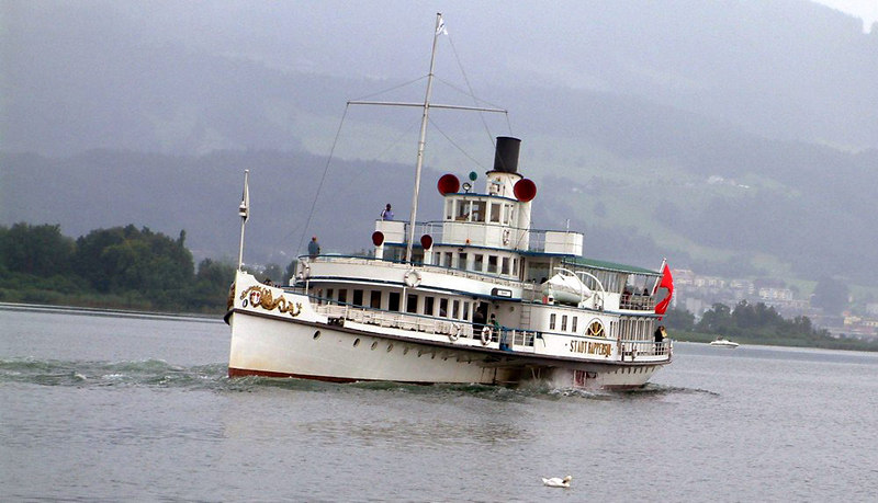 Paddle steamer Stadt Rapperswil going astern from Rapperswil on a damp, quiet Sunday heading for Zurich