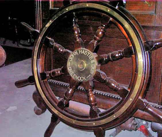 A tradition wooden ships wheel supplied by John Hastie & Co of Greenock. Later, tubular brass wheels were supplied more generally.