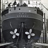 """ss UKI<br /> Yard No 753<br /> Launched: Wednesday, 21/03/1923 for the North Coast Steam Navigation Company, Sydney NSW<br /> Seen here from astern not long before launch with her twin propellers fitted. The propellers look to be painted so may be made from cast iron. Propellers of that type were manufactured by the firm of Andrew Strang at the Blair Foundry in Hurlford, Ayrshire. Larger and more expensive ships were fitted with propellers manufactured from bronze alloys. The principal supplier of such propellers on Clydeside was Bull's Metal & Melloid Co's Yoker foundry in Glasgow.<br /> <br /> Work is also progressing on preparing the launch 'ways'.<br /> Career: <a href=""""http://www.clydesite.co.uk/clydebuilt/viewship.asp?id=18077"""">http://www.clydesite.co.uk/clydebuilt/viewship.asp?id=18077</a>"""