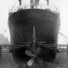 ss PLUME<br /> Yard No 790<br /> Triple expansion steam engine by David Rowan & Co Ltd, Glasgow<br /> Launched: Thursday, 24/06/1926 for the Vacuum Oil Company of London.<br /> A later view of PLUME in drydock, probably just prior to her going on trials,  when the hull would be cleaned and, possibly, painted to ensure minimum drag resistance during the trials. Note the rudimentary 'single plank' work staging with no safety rails, kick boards, etc that would be essential Health & Safety requirement now. Such conditions persisted well through the 20th Century.<br /> <br /> The ship's emergency steering wheel, which connected directly onto the rudder stock immediately below, can be seen in this view from astern. It would be used in the event of the failure of the normal steering gear. Typically, a steam or electric - hydraulic steering system, manufactured by specialist firms such as John Hastie & Co of the Kilblain Engine Works in Greenock,  Brown Brothers of the Rosebank Foundry in Edinburgh, MacTaggart, Scott & Co of the Loanhead Station Ironworks, Bow, McLachlan & Co of the Thistle Works  in Paisley and Thomas Reid & Son ,also based in Paisley, would be fitted to such ships.<br /> <br /> Remarkably, three of these five Scottish engineering firms are still practicing their trade in the first decade of the 21st Century, two of them as independent, privately-owned firms. Brown Brothers, MacTaggart, Scott and Thomas Reid have, in aggregate, over 400 years of experience in supplying marine equipment.