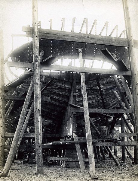 """ss UKI<br /> Yard No 753<br /> Launched: Wednesday, 21/03/1923 for the North Coast Steam Navigation Company, Sydney NSW<br /> Seen here in the early stages of construction with plates being set up in preparation for riveting to the frames. This view is at the stern of the vessel and they timber shoring and work staging is typical of the methods used over many decades. <br /> Career: <a href=""""http://www.clydesite.co.uk/clydebuilt/viewship.asp?id=18077"""">http://www.clydesite.co.uk/clydebuilt/viewship.asp?id=18077</a>"""