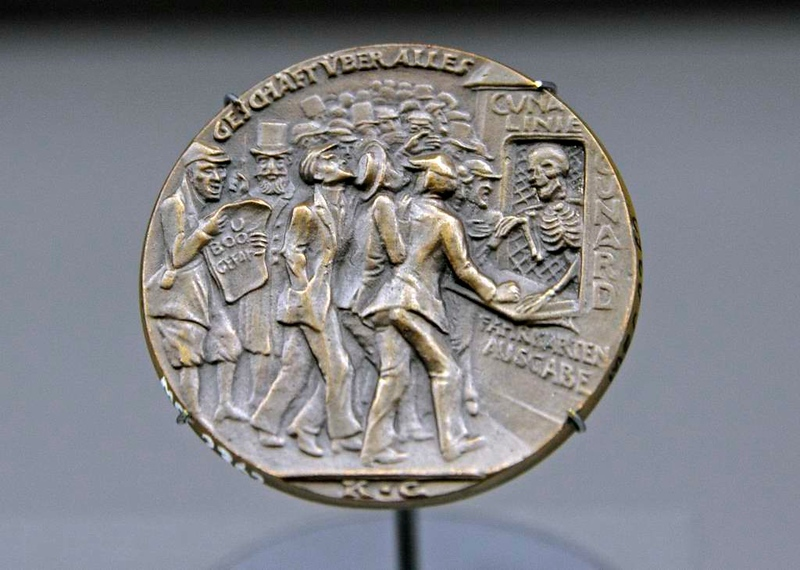 German Lusitania commemoration medallion, National Maritime Museum, Greenwich, 27 January 2015.  U-20 torpedoed the Cunard liner Lusitania off southern Ireland on 7 May 1915, killing 1201 passengers and crew.  A satirical German medallist produced this medallion to blame the British for the sinking.  Under a slogan meaning 'Business above all' Death sells tickets from the Cunard office as passengers ignore the U-boat warning ('U boot gefahr') posted by the Germans at the time of Lusitania's sailing from New York.  British naval intelligence made 300,000 slightly modified copies of the medallion for propaganda purposes.
