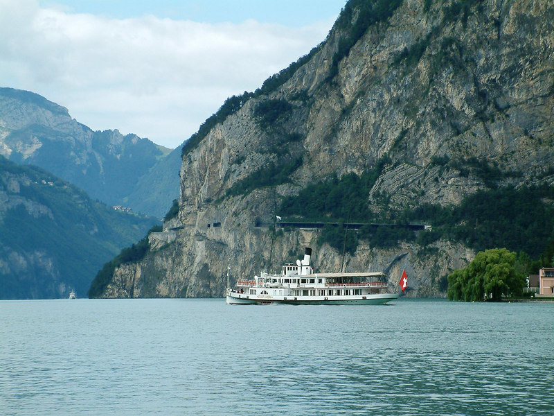 Paddle steamer Stadt Luzern passing under the Axenstrasse road and railway, cut through the mountainside near Fluelen