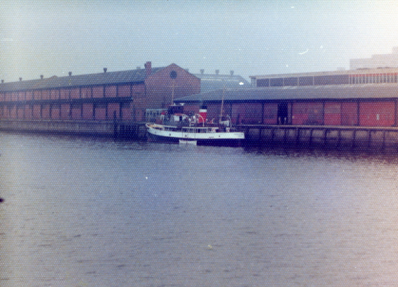 By 1977 the building of concrete offshore structures had gone out of fashion and the Ardyne yard was closed. Queen of Scots was little used and her Clyde career could have ended at that time. However, on the 15th July 1977 the preserved paddle steamer Waverley grounded on the Gantock Reef off Dunnon. She sustained severe damage to her hull and had to be withdrawn for 7 weeks for repair. Her owners, Waverley Steam Navigation Company of Glasgow, chartered Queen of Scots to maintain a reduced service during the paddler's absence. This view shows Queen of Scots being painted in WSN colours at Anderston Quay, Glasgow on 22nd July 1977