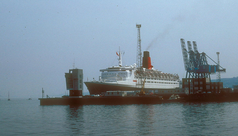 Twenty one years after her departure QE2 returned to the Clyde in 1990 to celebrate the 150th Anniversary of the founding of the Cunard Line. This recognised the crucial role played by Clydesiders in the formation of the Company in 1840. Cunard had been advised in London to travel to Glasgow to consult the emminent engineer Robert Napier on the design of ships for the new mail service to the USA. Napier advised that more and larger ships than Cunard had intended would be required. Cunard confided that he did not have sufficient capital to fund the additional, more expensive ships. Napier arranged for Cunard to meet with George Burns, a prominent Scottish shipowner. This resulted in the additional funding being provided by 'The Glasgow Proprietary in the British & North American Royal Mail Steam Packet Company' which did not become the Cunard Steamship Company until after Cunard's death. The Burns family remained influential in the Cunard Company for several generations. At the start of the 20th Century, the Chairman of Cunard was John Burns, Lord Inverclyde whose home was Castle Wemyss on the shores of the Clyde just north of Wemyss Bay.<br /> <br /> Picture by Stuart Cameron