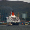 The tug Switzer Mallaig starts to cant the liner to face her bows seawards. The sandstone tower of the Victorian Greenock Town Hall can be seen above the liner.<br /> <br /> Picture by Stuart Cameron