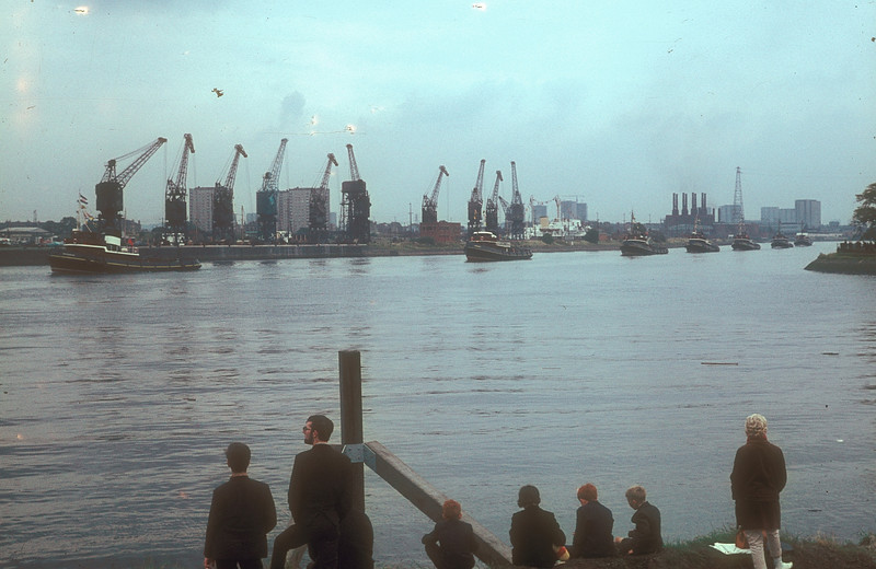 Seven Steel & Bennie tugs come down the river from Glasgow in procession  to take charge of the hull after launch<br /> <br /> Note the collection of cranes (including 5 luffing cranes) arranged along the south wall of the Rothesay Dock - the dock was still a significant minerals and coal handing facility in 1967 - this had been the major work of the dock since its inception in the first decade of the 20th Century suplementing the  and minerals berths on the north wall of the Queens Dock in Finnieston (where the SECC now stands). Coal was still a major cargo at Rothesay dock well into the 1980s. The quay wall between the dock and the river was probably not designed to accommodate such heavy loads over prolonged periods and parts of the wall were cordoned off and signed as unsafe during the 1990s, by which time all of the cranes seen above had gone for 'razorblades'. The building with the 8 chimneys above the fourth tug is the Clyde Valley Generating Company's Yoker Power Station boilerhouse. Yoker Power Station, together with Dalmarnock Power Station - also on the north side of the river, were the largest power stations in Scotland in the 1950s and had been the first Scottish generating stations added to the National (Electricity distribution) Grid. Both used river water as coolant in the condensers avoiding the need for large concrete cooling towers. Just to the right of the station is one of the two very high pylon towers that carried the high voltage transmission lines over the river to a distibution substation in Renfrew. The station also served the Braehead Power Station which occupied the site on which the shopping mall now stands<br /> <br /> Picture by the late Mr William Davies