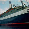 Queen Elizabeth 2 fitting out in the UCS Clydebank (ex John Brown's) shipyard at Clydebank on 18th May 1968 - viewed from the Caledonian Steam Packet Company's paddle steamer Caledonia, which was on a charter sailing from Glasgow Bridge Wharf SS to Loch Riddon for Rutherglen West Parish Church.  Caledonia had attended the liner's launch 8 months earlier.<br /> <br /> Photo by Stuart Cameron