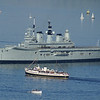 Balmoral heading round the bow of the anchored Ark Royal - in the foreground is the classic private motor yacht Fenella