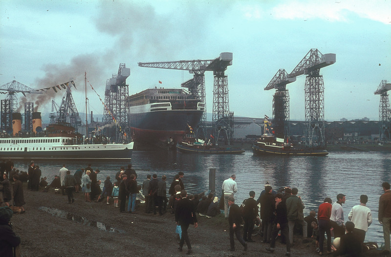 The well known Clyde turbine steamer Duchess of Hamilton, flagship of the Clyde fleet, under the command of the legendary Captain Fergus B Murdoch MBE, passing the new liner as she arrives from downriver for the launch – she berthed in Rothesay Dock.<br /> <br /> Picture by the late Mr William Davies