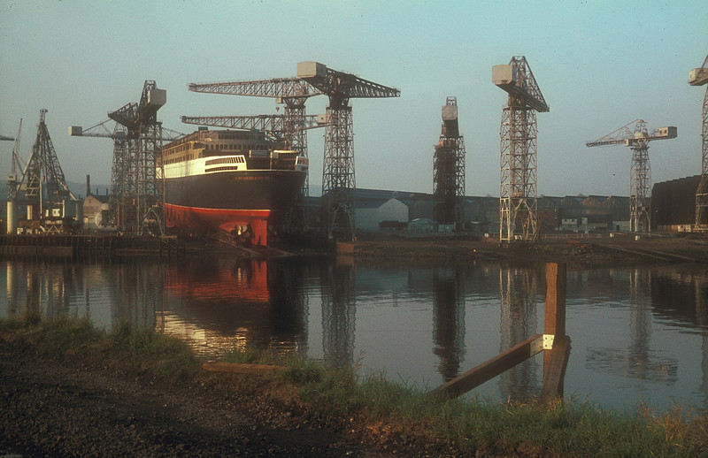 Yard No 736 at Clydebank on the evening of 19th September 1967, the eve of her launch<br /> <br /> Another view of the Arrol hammerheads - six on the main building berth and six on the secondary berth of the east yard. More of these cranes were located alongside the long building berth in the West Yard (around 6 cranes from memory), downstream of the fitting out basin.<br /> <br /> Picture by the late Mr William Davies