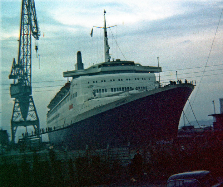 """Queen Elizabeth 2 completing outfitting and undergoing pre-trials hull cleaning in the Firth of Clyde Drydock Company's large drydock at Inchgreen in Greenock. This set her aside from the other large Clydebuilt Cunarders, which had to be drydocked in the south as there was not a large enough drydock on the Clyde. The QE2's predecessor, the Clydebank-built Queen Elizabeth (which had only been seen back on the Clyde during the Second World War) made one visit in her merchant service day's - to the new Inchgreen drydock for a refit in 1965. the Queen Mary never returned to the Clyde after her war sevice ended.<br /> <br /> A tremendous sequence of photos showing the construction of the Firth of Clyde Drydock can be seen in another 'Pudzeoch' Gallery<br /> <br />  <a href=""""http://pudzeoch.smugmug.com/Other/Greenock-Harbour-Works/4886383_xqYfo#291462333_ZQUWm"""">http://pudzeoch.smugmug.com/Other/Greenock-Harbour-Works/4886383_xqYfo#291462333_ZQUWm</a><br /> <br /> Picture by Stuart Cameron"""