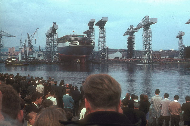 On the afternoon high tide on 20th September 1967, Yard No 736 was named 'Queen Elizabeth the Second' by HM Queen Elizabeth.<br /> <br /> Quite unusual to see all the crane jibs so uniformly aligned - the last one had fallen into line just a few minutes earlier after lifting the final access gangway away from the vessel's hull.<br /> <br /> Picture by the late Mr William Davies
