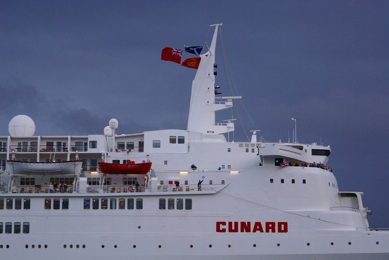 """Passengers on QE2 wave to passengers on Balmoral. The ship is displaying three flags on her mast. On the left is the Red Ensign (or Red Duster), the venerable symbol of the British merchant navy. Top right is the blue and white Saltire of Scotland. Bottom right is the houseflag of the Cunard Steamship Company - a red flag with a Lion Rampant  superimposed in gold. The Cunard houseflag was based on that of shipping firm G & J Burns of Glasgow (which was blue with the gold Lion Rampant). <br /> <br /> The first ever Cunard liner, the Britannia , was built on the Clyde in 1840 - see<br /> <br />  <a href=""""http://www.clydesite.co.uk/clydebuilt/viewship.asp?id=533"""">http://www.clydesite.co.uk/clydebuilt/viewship.asp?id=533</a><br /> <br /> Picture by Stuart Cameron"""