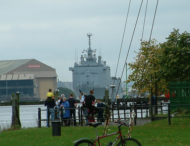 Visiting ships of any type still draw Clydesiders to the river; French naval ship Orage passing BAE Systems Scotstoun shipyard on her way to the sea with onlookers on Renfrew's Ferry Green.