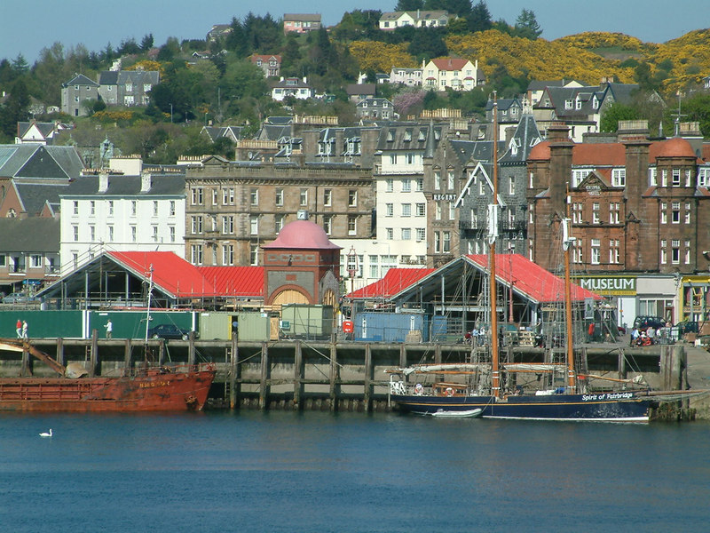 The North Pier at Oban was undergoing major renovation in 2003. All buildings on the pier, apart from the 1927 clock tower, were replaced by modern restaurants and public conveniences. The two masted vessel on the right is the Spirit of Fairbridge, formerly known as Spirit of Scotland when owned by the chairman of Scottish Nuclear plc.