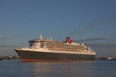 QM2 in full early morning sunshine as she picks her way carefully past Town Quay, Southampton heading to berth 101 after completing a trans Atlantic crossing from New York.