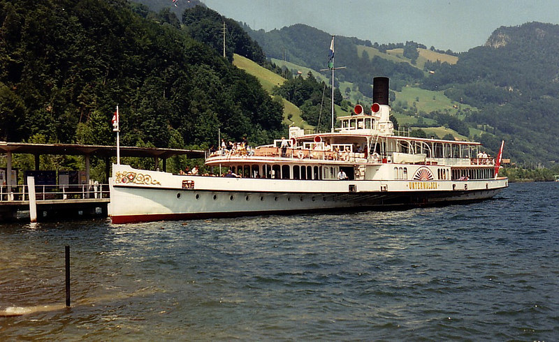 The trip to the summit of 7000-foot Mount Pilatus commences by sailing in the veteran paddle steamer Unterwalden, built in 1903 by Escher Wyss in Zurich, and still steaming on her original Scotch boilers a century later. Unterwalden sails from Luzern to Alpnachsstad, passing under the low level Acheregg Bridge en route. This requires the retraction of several parts of her superstructure. From the early 1960s until the mid 1990s her 2 masts were racked down into her hull and she is seen here at Alpnachsstad in 1992 with her aft (main) mast so retracted. At this pier it is a short walk to the bottom station of the Pilatusbahm, the railway to the top of Mount Pilatus