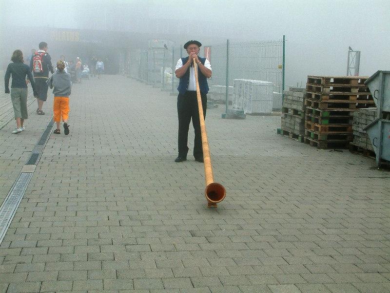 An Alphorn player near the misty summit of Pilatus