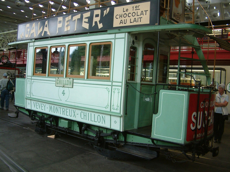 Electric Tramcar Ce 1/2 No 4, built in 1888 to run along the 'Riviera' shore of Lake Leman between the resorts of Vevey and Montreux and the ancient Castle of Chillon (See the 'Lake Leman and its Steamers' gallery). This tram used the system developed by Werner von Seimens in 1881. It comprised of two overhead copper tubes, forming two sides of the current, with slots on their undersides. The current was transferred to contacts towed on a sledge. The traction motor was located between the axles of the tram and drove oneof them through gear wheels with herring-bone shaped teeth.