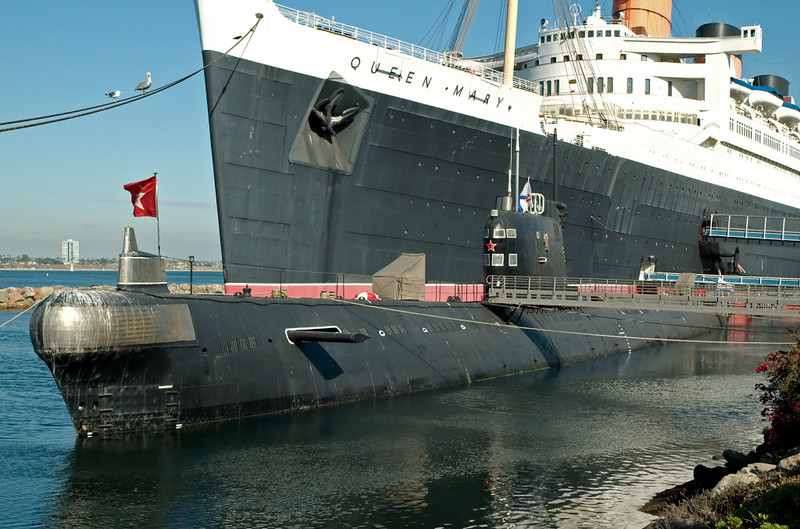 Soviet Foxtrot class submarine B-427 'Scorpion' & Queen Mary, Long Beach, California, 2 October 2006. The 1,952 ton (surfaced) diesel-electric SSK (hunter-killer submarine) nestles beneath the retired 81,237 ton Cunarder.  58 Foxtrots were built for the Soviet Navy 1957 - 1971.  They had all been decommissioned by 2000.  16 other boats were built for other navies.