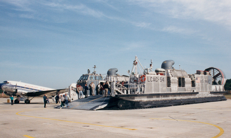 Date: unknown - Location: Pensacola, FL<br /> Class:  Landing Craft Air Cushion (LCAC)<br /> Hull Number:  54<br /> Misc:  LCAC-54 sits on the ramp at NAS Pensacola during an open house.  The LCAC sits next to a DC-3 in Piedmont markings.