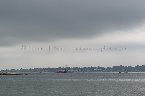 The USS Springfield (SSN-761) with the tug Paul A. Wronowski alongside head north in the Thames River under some gloomy skies