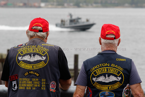 A pair of Submarine Veterans watch a US Navy patrol boat speed past in advance of the USS Springfield