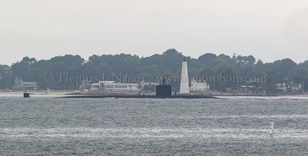 The USS Springfield (SSN-761) passing by the historic New London Harbor Light