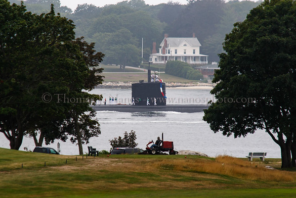 The US Navy Los Angeles class fast attach submarine USS Springfield (SSN 761) returns from a deployment to the Sub Base in Groton, Connecticut as a groundskeeper at the Shenecossett Golf Course takes a break from mowing, by watching the submarine pass by.