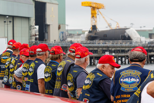 A group of Submarine Veterans gathered at an overlook north of the Electric Boat shipyard in Groton. Visible in the background is the aft hull section of a future Virginia class submarine.