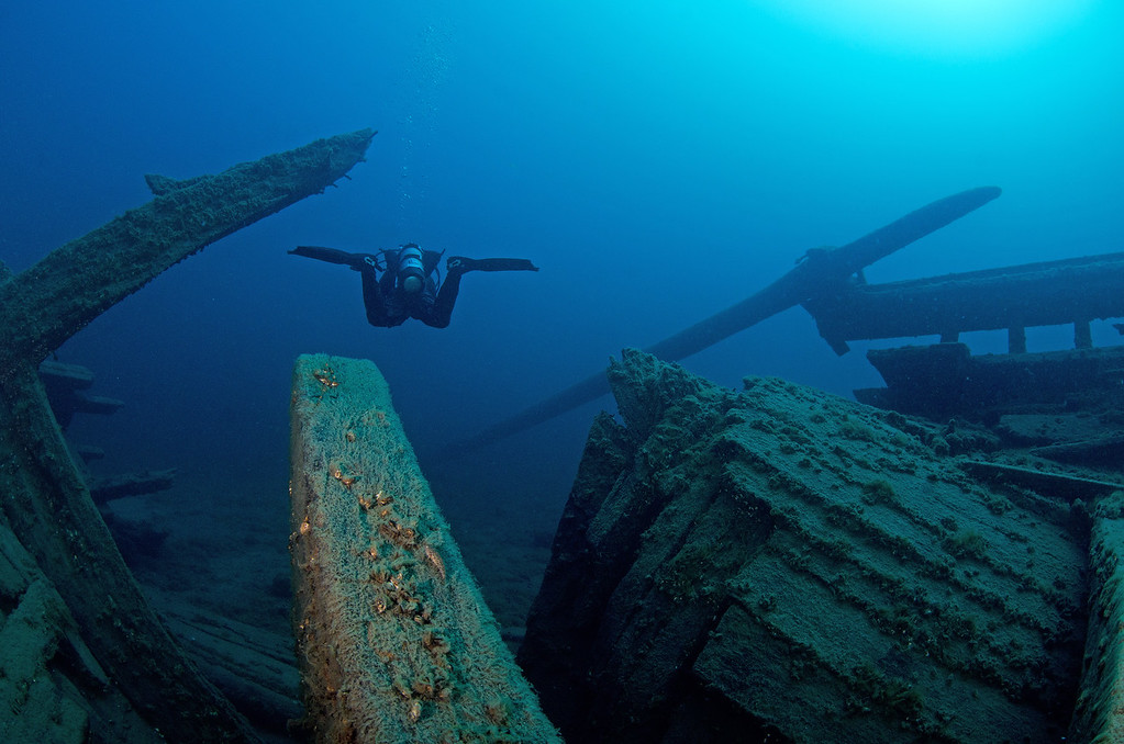 Perfectly trimmed out, this diver swims over the broken stern of Arabia