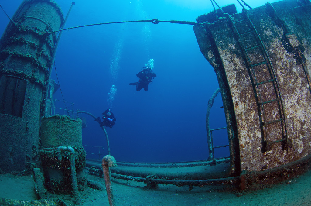 Two divers explore the superstructure of this little ship.