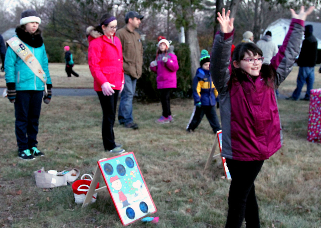 . All smiles after winning in the bean bag toss game is Melissa Messenheimer 7 of Shirley, in back L-R, are Sophie Brown,13, and Katie Brauckmiller, 13, both members of Venture Crew #34, a co-ed scout troop, all at the Shirley tree lighting. Nashoba Valley Voice Photo/David H. Brow