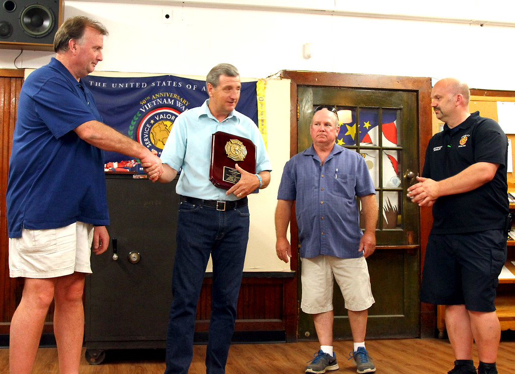 . Shirley Fire Dept. members present Chief Dennis Levesque with a plaque, L-R, Shirley Deputy Bill Callahan, Chief Levesque, Shirley FF Billy Poitras, and Lt. Al Deshler. Nashoba Valley Voice Photo by David H. Brow.