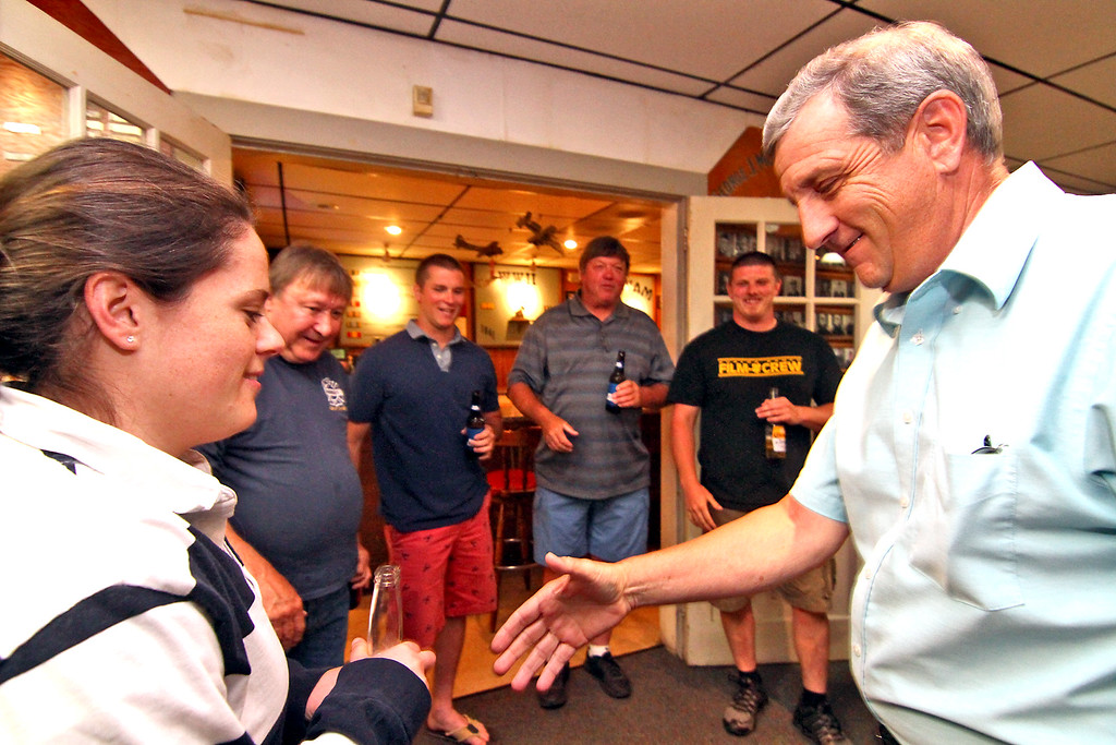 . Shirley firefighter Mackenzie Flagg,on left, shakes hands with her boss, Shirley Fire Chief Dennis Levesque as he arrives at a party to celebrate his 40 years of service. Nashoba Valley Voice Photo by David H. Brow.