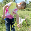 Jaden Rainey, 6, was helping his mom Felicia Harwood, both of Leominster, tend to their plants  at the Sholan Farms community gardens on Tuesday afternoon just before they went fishing at Barrett Park. SENTINEL & ENTERPRISE/JOHN LOVE