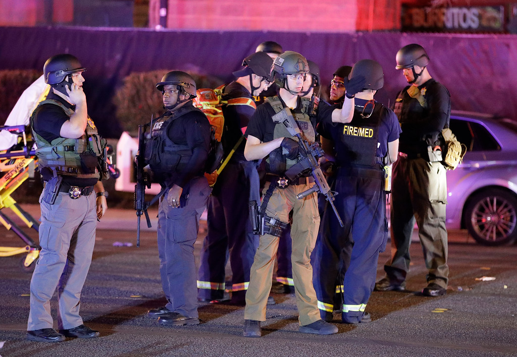 . Police officers stand at the scene of a shooting near the Mandalay Bay resort and casino on the Las Vegas Strip, Monday, Oct. 2, 2017, in Las Vegas. Multiple victims were being transported to hospitals after a shooting late Sunday at a music festival on the Las Vegas Strip. (AP Photo/John Locher)
