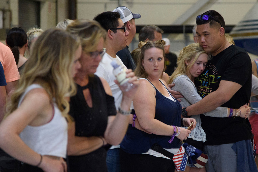 . Concertgoers embrace as they wait early Monday, Oct. 2, 2017, inside the Sands Corporation plane hangar after a mass shooting in which dozens were killed  at the Route 91 Harvest country festival early Sunday. (Al Powers/Invision/AP)