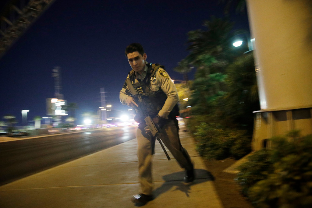 . A police officer runs along a sidewalk near a shooting near the Mandalay Bay resort and casino on the Las Vegas Strip, Sunday, Oct. 1, 2017, in Las Vegas. (AP Photo/John Locher)