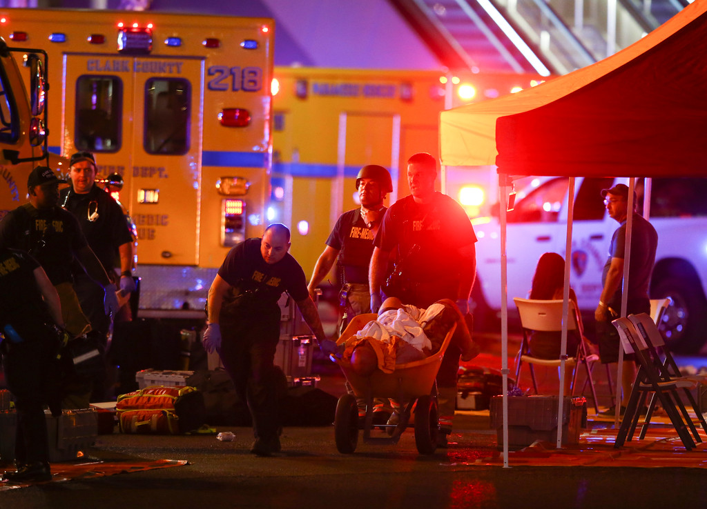. A wounded person is walked in on a wheelbarrow as Las Vegas police respond during an active shooter situation on the Las Vegas Stirp in Las Vegas  Sunday, Oct. 1, 2017. Multiple victims were being transported to hospitals after a shooting late Sunday at a music festival on the Las Vegas Strip. (Chase Stevens/Las Vegas Review-Journal via AP)