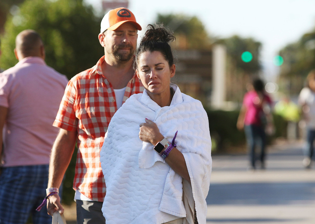 . Melissah Burke and her husband Stephen, of Seattle, walk along the Las Vegas Strip near Mandalay Bay hotel and casino Monday, Oct. 2, 2017, in Las Vegas. The couple, who were attending the music festival last night where a mass shooting occurred, found refuge in a nearby apartment and casino. (AP Photo/Ronda Churchill)