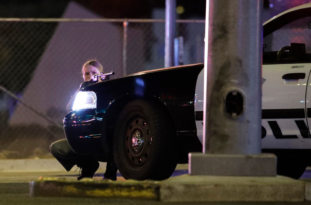 . A police officer takes cover behind a police vehicle during a shooting near the Mandalay Bay resort and casino on the Las Vegas Strip, Sunday, Oct. 1, 2017, in Las Vegas. (AP Photo/John Locher)