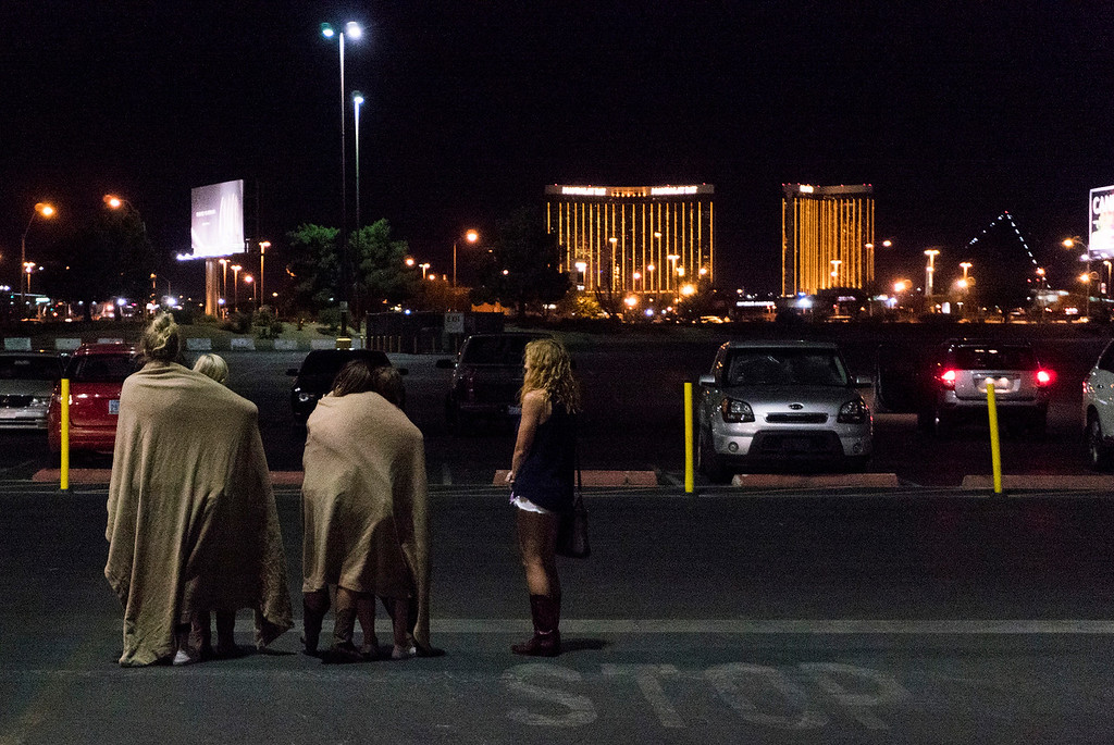 . A group of women wait for their ride outside the Thomas & Mack center, which served as a refuge, following a mass shooting at the Route 91 music festival along the Las Vegas Strip, Monday, Oct. 2, 2017, in Las Vegas. (Yasmina Chavez/Las Vegas Sun via AP)