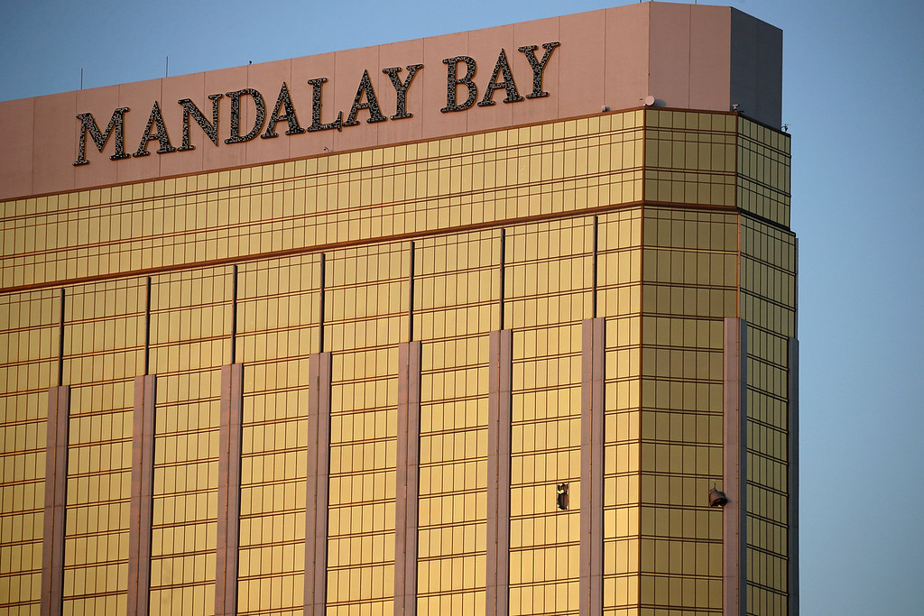 . Drapes billow out of broken windows at the Mandalay Bay resort and casino Monday, Oct. 2, 2017, on the Las Vegas Strip following a deadly shooting at a music festival in Las Vegas. A gunman was found dead inside a hotel room. (AP Photo/John Locher)