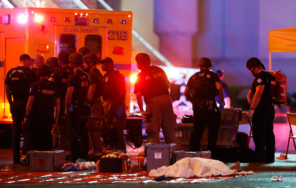 . A body is covered with a sheet after a mass shooting in which dozens were killed at a music festival on the Las Vegas Strip on Sunday, Oct. 1, 2017. (Steve Marcus/Las Vegas Sun via AP)