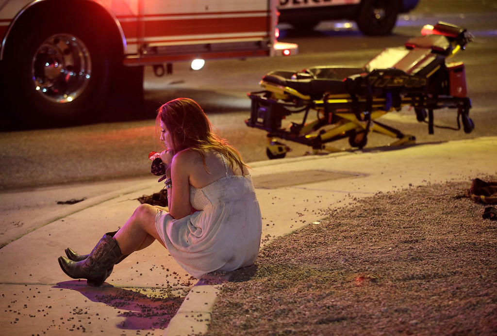 . A woman sits on a curb at the scene of a shooting outside of a music festival along the Las Vegas Strip, Monday, Oct. 2, 2017, in Las Vegas. Multiple victims were being transported to hospitals after a shooting late Sunday at a music festival on the Las Vegas Strip. (AP Photo/John Locher)
