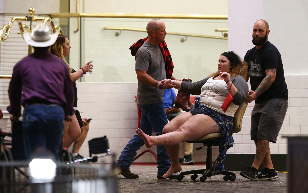 . A wounded woman is moved outside the Tropicana during an active shooter situation on the Las Vegas Strip in Las Vegas Sunday, Oct. 1, 2017. Multiple victims were being transported to hospitals after a shooting late Sunday at a music festival on the Las Vegas Strip. (Chase Stevens/Las Vegas Review-Journal via AP)